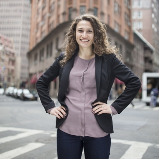 Female student dressed business casual standing in front of a building in Manhattan