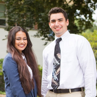 A female and male students dressed in business attire.